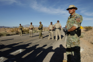 Federal law enforcement officers block a road at the Lake Mead National Recreation Area near Overton, Nev. Thursday, April 10, 2014. In the foreground are the shadows of protestors. Two people were detained while protesting the roundup of cattle owned by Cliven Bundy on the road. (John Locher/Las Vegas Review-Journal)